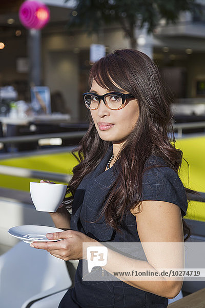 'Professional businesswoman taking a break with a cup of coffee in a shopping centre; St. Albert  Alberta  Canada'