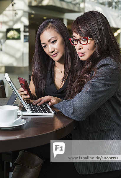 'Businesswoman training a co-worker in a coffee shop at a shopping complex; St. Albert  Alberta  Canada'