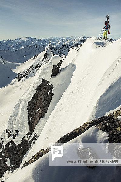 Tiefblick auf den Skifahrer  der auf einem schneebedeckten Berg steht.