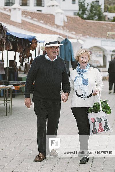 Volle Länge des Seniorenpaares beim Spaziergang auf dem Straßenmarkt