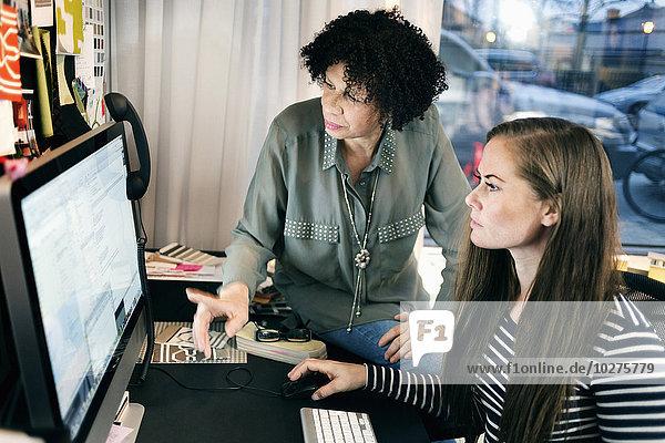 Geschäftsfrauen  die am Computer im Büro arbeiten