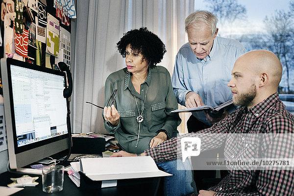 Geschäftsleute  die am Computertisch im Büro arbeiten