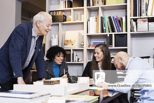 Fröhliche multiethnische Geschäftsleute diskutieren über das Projekt im Büro