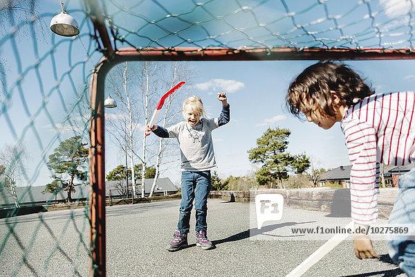 Aufgeregtes Mädchen beim Hockeyspielen mit dem Jungen auf dem Hof