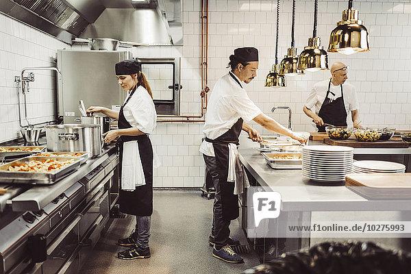 Köchinnen und Köche bei der Zubereitung von Speisen in der Großküche