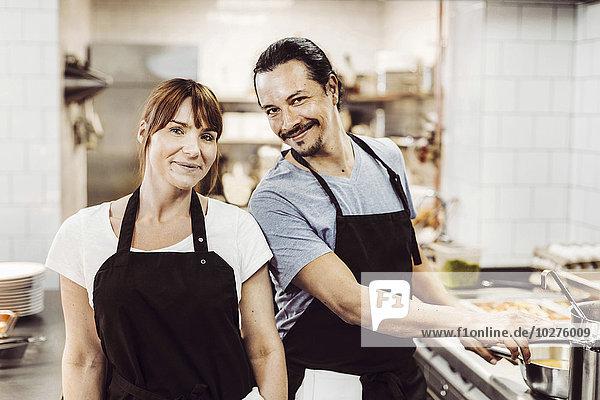 Porträt von lächelnden Köchen in der Großküche