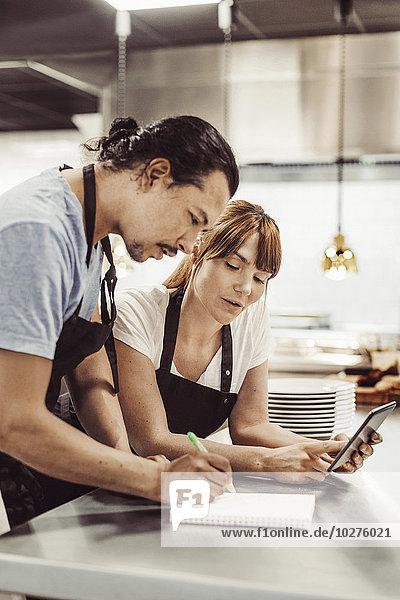 Köche mit digitalem Tablett beim Schreiben von Rezepten an der gewerblichen Küchentheke