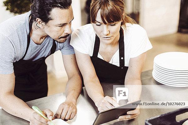 Hochwinkelansicht von Köchen mit digitalem Tablett beim Schreiben von Rezepten in der Großküche