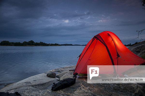Zelt auf Felsen am Seeufer in der Abenddämmerung