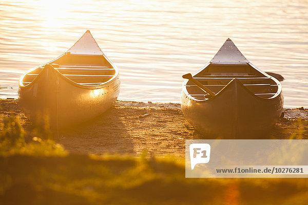 Kanus  die bei Sonnenuntergang am Seeufer anlegen