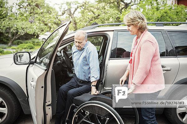 Mann beim Aussteigen aus dem Auto im Rollstuhl von einer Frau gehalten