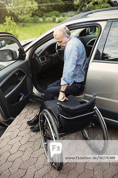 Behinderter Mann beim Aussteigen aus dem Auto im Rollstuhl