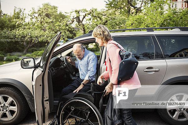 Behinderter Mann beim Aussteigen aus dem Auto auf einem Rollstuhl  der von einer Frau gehalten wird.