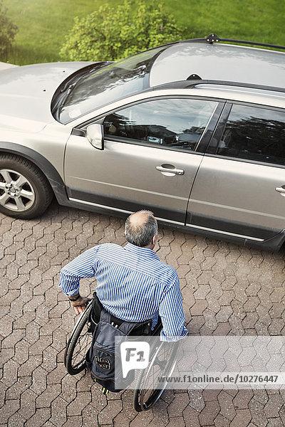 Hochwinkelansicht eines reifen Mannes im Rollstuhl  der sich auf der Straße in Richtung Auto bewegt.