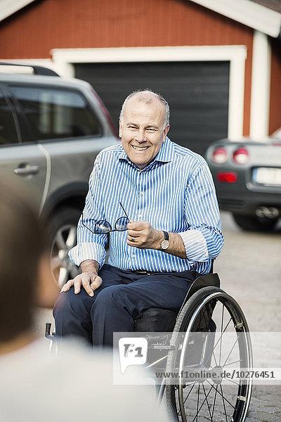 Glücklicher Vater im Rollstuhl  der den Sohn auf der Straße ansieht.