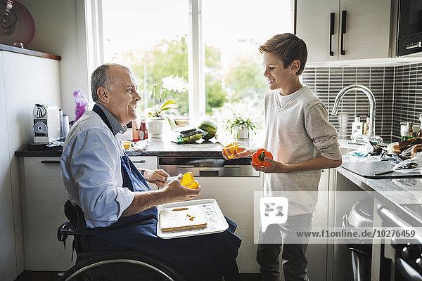 Glücklicher behinderter Vater im Rollstuhl bei der Zubereitung des Essens mit Sohn in der Küche