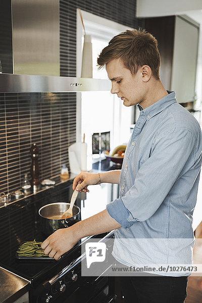 Junger Mann bei der Zubereitung von Speisen in der Küche