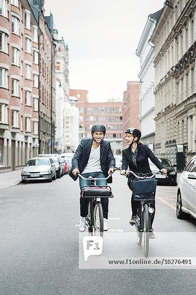 Glückliche Geschäftsleute auf Fahrrädern in der Stadt