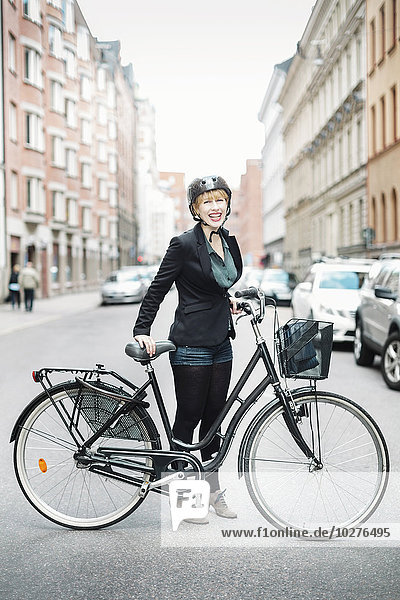 Portrait of happy businesswoman with bicycle standing on city street