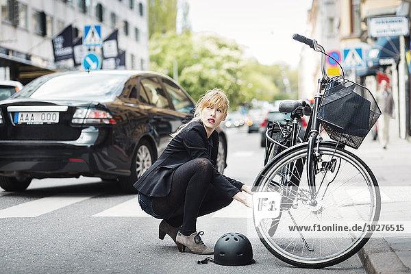 Geschäftsfrau schaut weg  während sie das Fahrrad auf der Straße repariert.