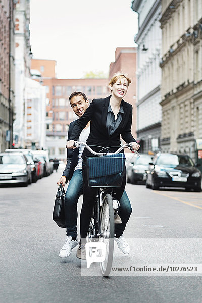Happy business people riding bicycle on city street