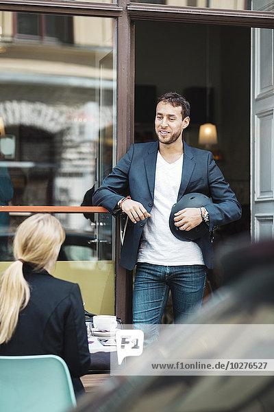 Lächelnder Geschäftsmann mit Helm beim Gespräch mit Kollegen im Straßencafé