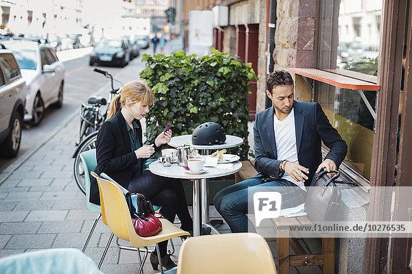 Berufspendler sitzen im Straßencafé