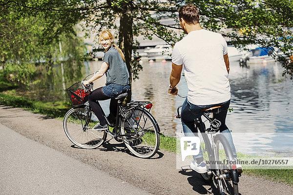 Fröhliche Geschäftsfrau beim Fahrradfahren auf der Straße am See
