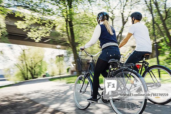 Rückansicht von Geschäftsleuten beim Fahrradfahren auf der Straße