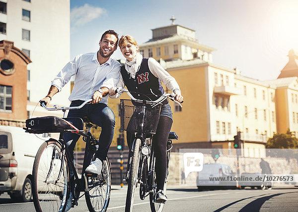 Fröhliche Geschäftsleute mit dem Fahrrad auf der Stadtstraße