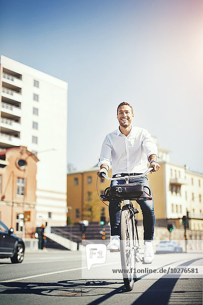 Happy businessman riding bicycle on city street against blue sky