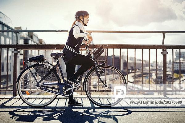 Seitenansicht der Geschäftsfrau mit auf der Brücke stehendem Fahrrad