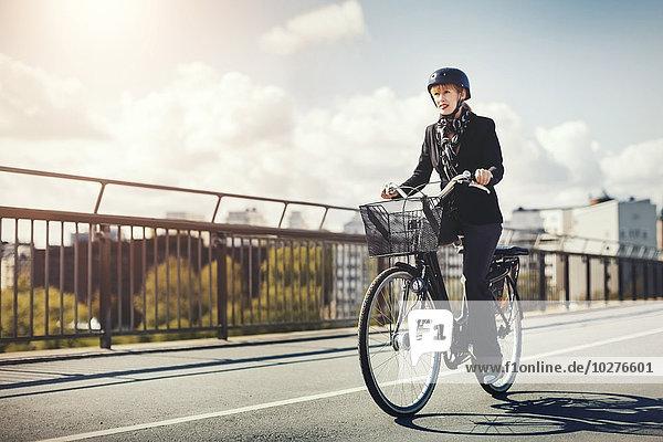 Geschäftsfrau fährt Fahrrad auf der Brücke in der Stadt