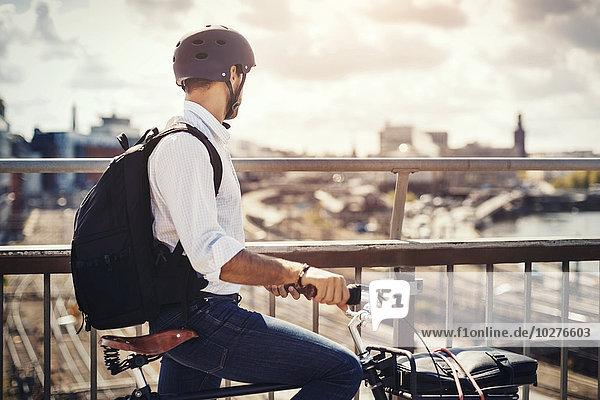 Geschäftsmann mit Fahrrad und Blick auf die Stadt  während er auf der Brücke steht.