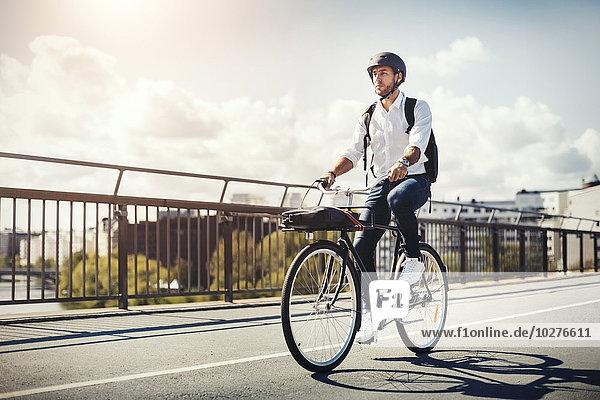 Geschäftsmann mit dem Fahrrad auf der Brücke gegen den Himmel