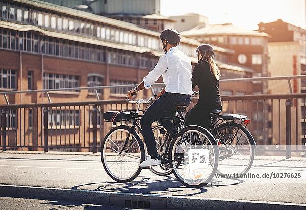 Rückansicht von Geschäftsleuten  die auf der Brücke Fahrrad fahren
