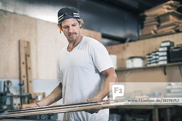 Schreiner beim Betrachten von Holzbrettern in der Werkstatt