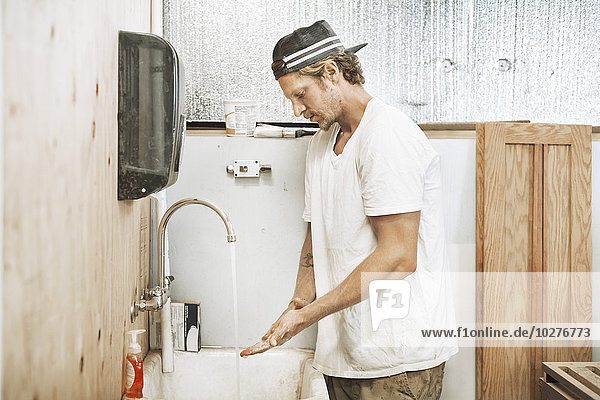 Schreiner beim Händewaschen in der Werkstatt