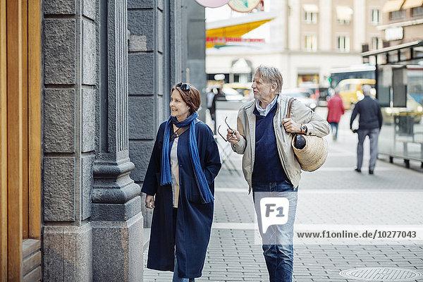 Seniorenpaar schaut auf das Schaufenster  während es auf der Stadtstraße geht.