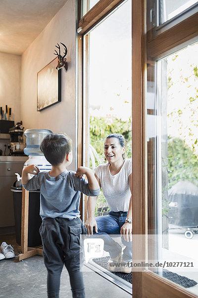 Glückliche Frau  die den Sohn ansieht  während sie sich auf dem Eingang hockt.