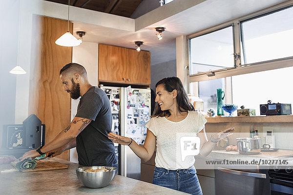 Glückliche Frau gestikuliert  während sie mit einem Mann spricht  der in der Küche Gemüse schneidet.
