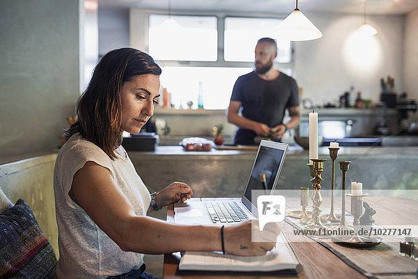 Seitenansicht der Frau  die am Esstisch arbeitet  während der Mann im Hintergrund steht.