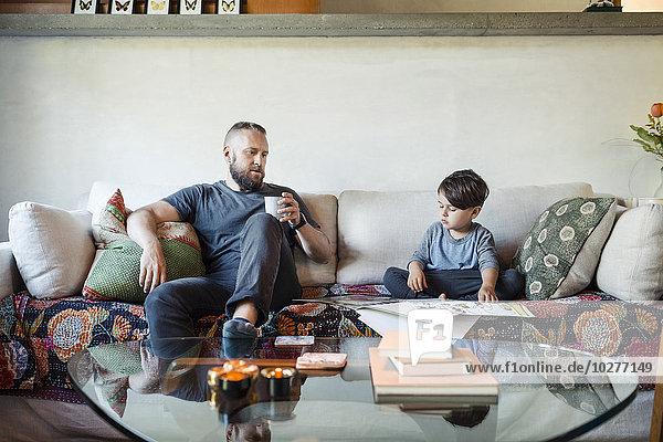 Vater hält Kaffeetasse und unterstützt den Sohn bei den Hausaufgaben zu Hause.