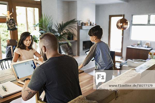 Rückansicht des Mannes  der am Laptop arbeitet  während die Familie am Esstisch im Haus sitzt.