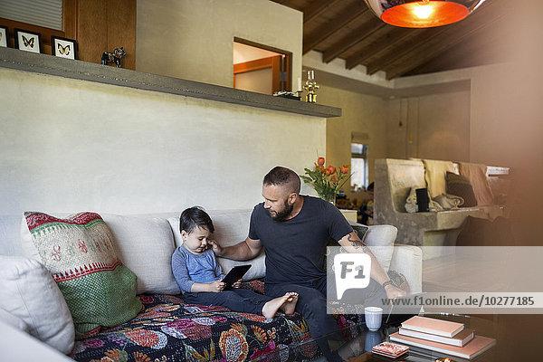 Vater im Gespräch mit Sohn über Tablet-Computer im Wohnzimmer