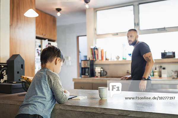 Father looking at son using digital tablet in kitchen