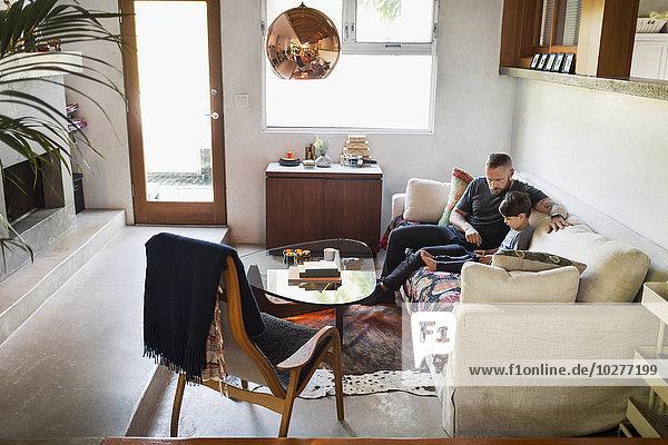 Vater und Sohn mit digitalem Tablett auf dem Sofa zu Hause