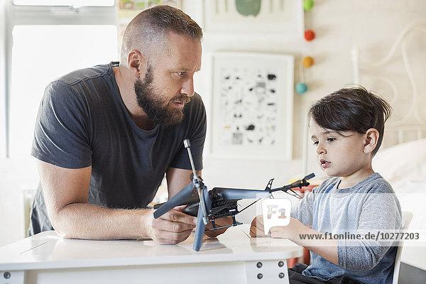 Vater hält Spielzeugfahrzeug  während er den Sohn im Schlafzimmer ansieht