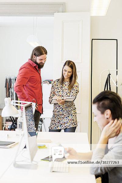 Geschäftsleute diskutieren über Dokumente im Kreativbüro