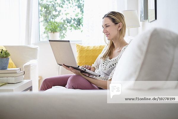 Woman with laptop sitting on sofa
